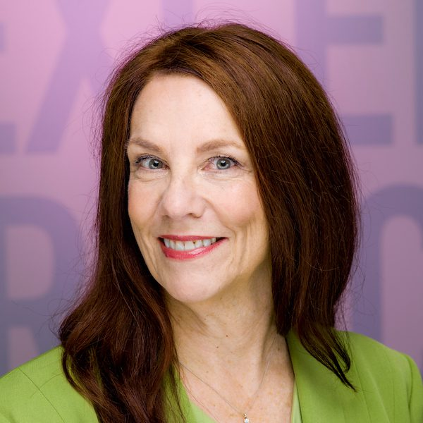 head shot of Kathryn Woodcock, a white woman with long auburn hair, wearing apple-green jacket and top, seated in front of mauve wall with unreadable lettering
