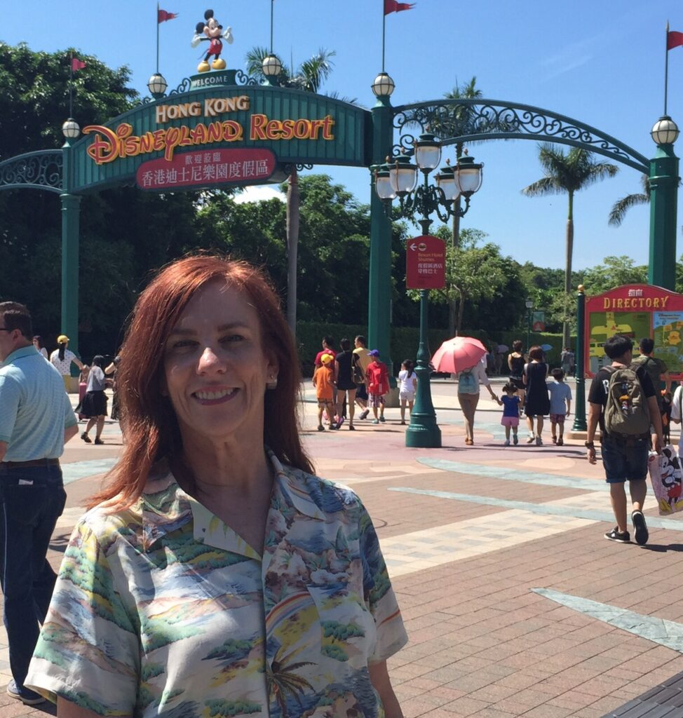 Kathryn Woodcock (white woman, auburn hair, (seen only from elbows up) poses in front of entrance sign of Hong Kong Disneyland Resort, on a sunny day, blue sky, palm trees, not too crowded; wearing aloha shirt