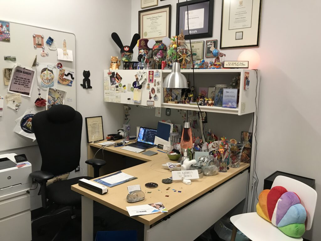 ivory office desk with blonde wood top, ivory wall-mounted overhead bin, with lots of toys and a lava lamp; a white chair in the foreground has an NBC peacock throw pillow