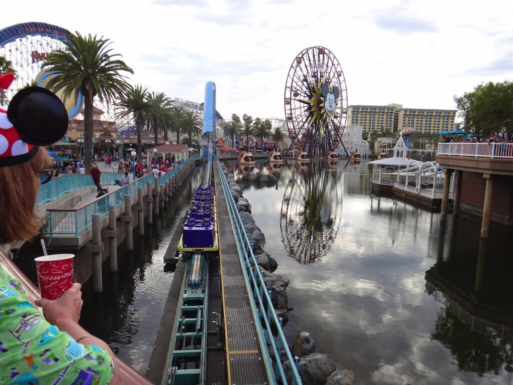 View of launch track of California Screamin' coaster at Disney's California Adventure, with Mickey's Fun Wheel in distance, seen over the shoulder of Kathryn Woodcock, only shoulder and part of head are visible, wearing aloha shirt and Minnie Mouse ear hat