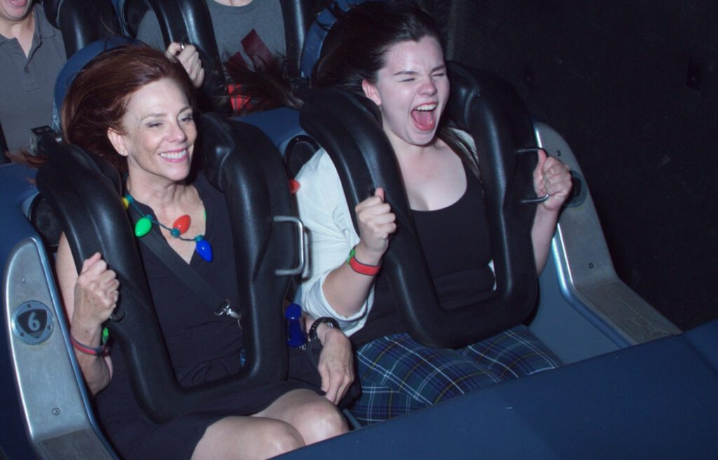 Kathryn and Ruby (white women) riding roller coaster. Kathryn is smiling while Ruby is screaming.