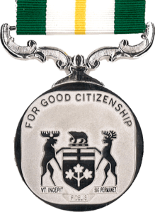 silver circular medal 36-mm diameter, Coat of Arms of the Province of Ontario fills the bottom 2/3rd of the disc with the words FOR GOOD CITIZENSHIP around the upper rim, suspended on scroll type mounting from a green ribbon 32-mm wide with central white stripe (15-mm) within which is centred a single gold stripe (3-mm)
