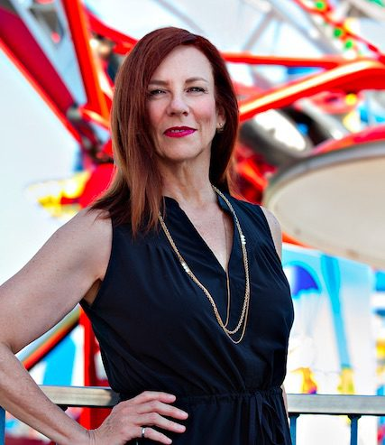Photo courtesy of TSSA, from Safety Impact Award profile: Kathryn Woodcock, white woman, auburn hair, in sleeveless black dress, gold chain poses in front of roller coaster at Fun Spot, Orlando