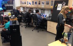 THRILL Lab workspace, blonde wood cabinets, black desktop, pictures taped on cupboard doors; several diverse students work on various things in the space.