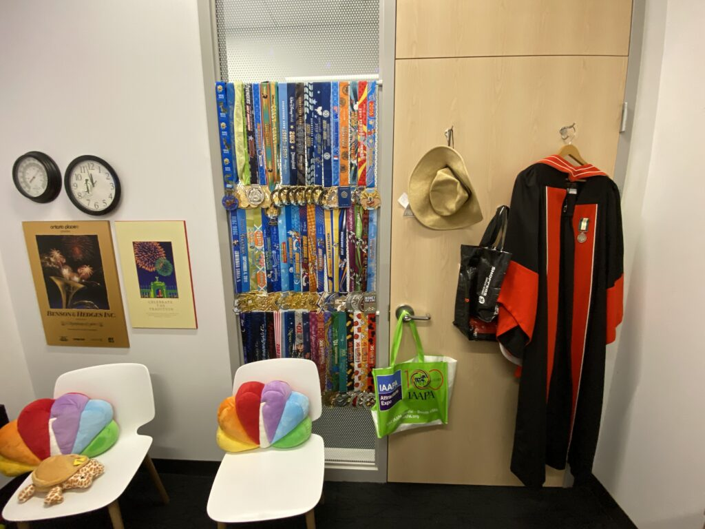 View of office door from inside: visible UofT doctoral robe with medal on facing, sun hat, two white chairs both with NBC peacock throw cushions, two Symphony of Fire posters on wall, below clock and thermometer, and dozens of half marathon medals hung up as window covering beside door