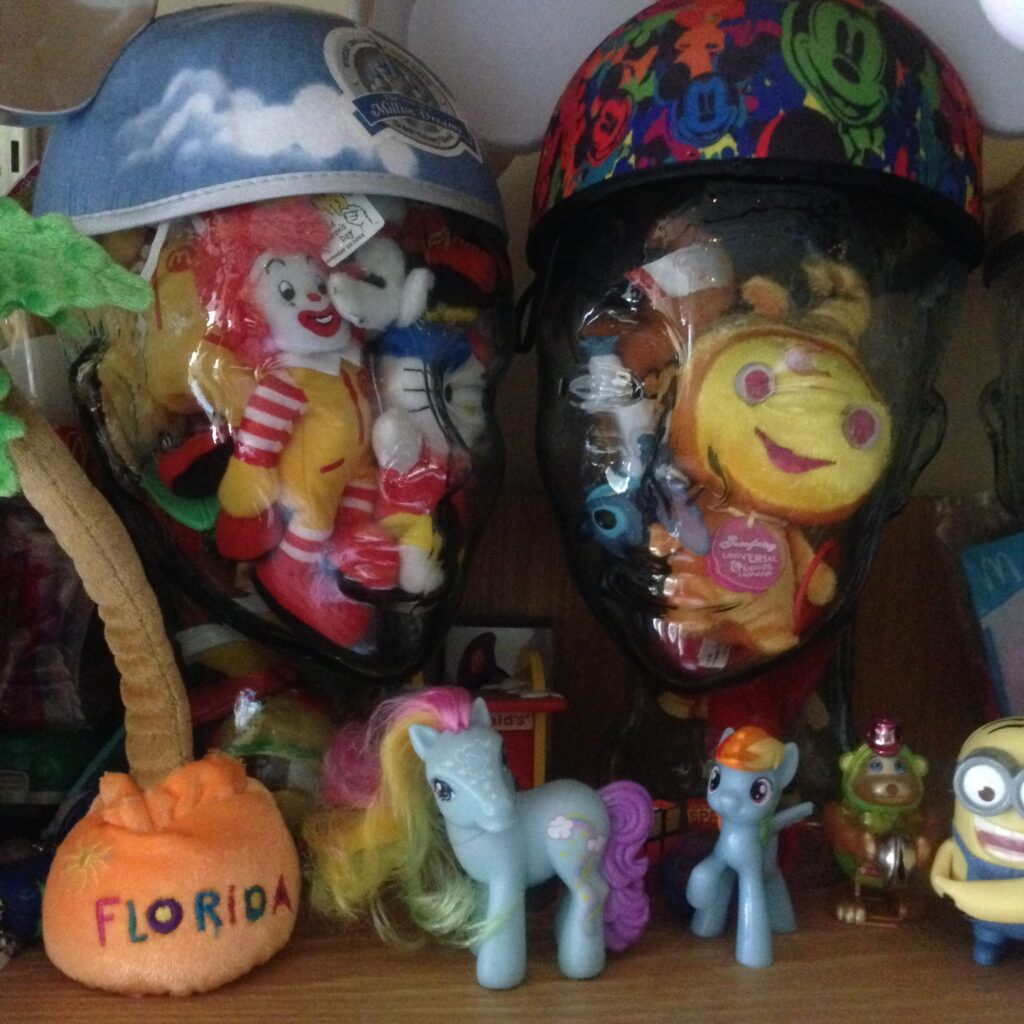 """Two glass wig stands wearing Disney mouse ears stuffed with a variety of happy-meal toys and souvenir plush items, with some """"my little pony"""" etc. in foreground - purely whimsical decorative image"""
