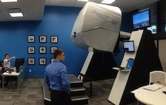 A white man in blue shirt stands with back to camera in room with blue walls, some framed black and white photos, and a large white-gloss coated motion simulator unit